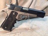 colt mk iv series 70 gold cup national match slide and barrel on top of amt stainless frame .45 caliber acp automatic