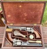 True Cased Pair of Factory Engraved Donut Scroll Colt Model 1851 Navy Revolvers